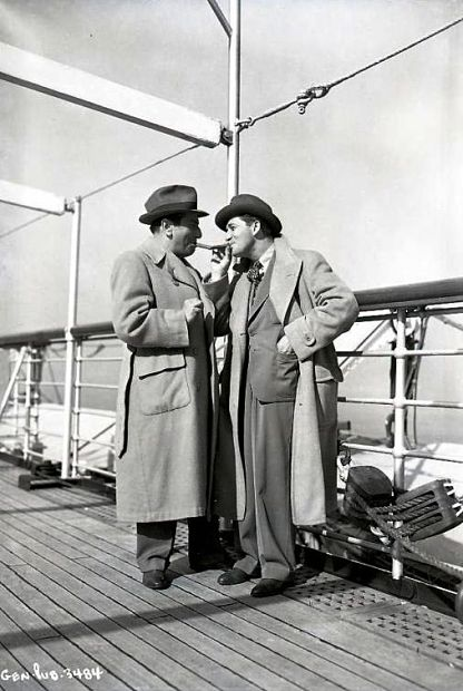 EL_Directors Ernst Lubitsch and Mervyn LeRoy compare the size of their cigars