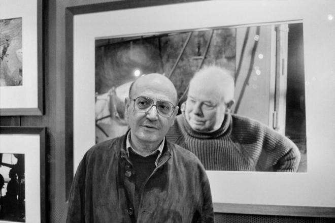 Theo ANGELOPOULOS posing in front of a portrait of Jean Renoir, photographed by Rene BURRI. 1998. by Guy Le Querrec