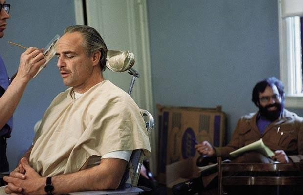 Francis Ford Coppola waiting as Dick Smith applies makeup to Marlon Brando