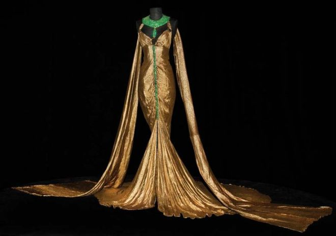 Claudette Colbert signature gold-lamé and emerald boudoir gown by Travis Banton from 1934's Cleopatra - sold at a 2011 auction for forty thousand dollars.