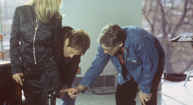 David Cronenberg and James Spader examine Rosanna Arquette's braces on the set of Crash