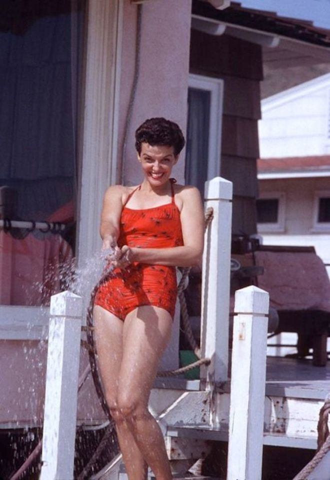 Jane Russell having fun with a hose at her Malibu Beach House, circa 1957