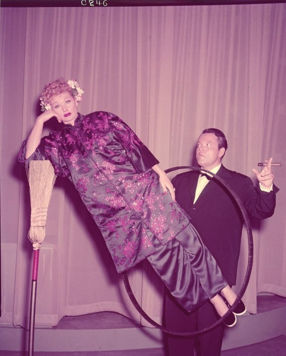 "9th_Orson Welles performing the ""Broomstick Suspension"" magic trick with Lucille Ball during the filming of the I Love Lucy episode, ""Lucy Meets Orson Welles"" (1956)"