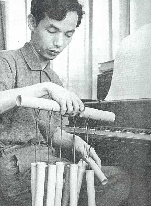 27_Composer Toru Takemitsu holding a vernacular instrument made from bamboo, 1961..jpg