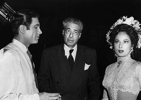 Director Irving Pichel between the stars of Temptation, Charles Korvin and Merle Oberon.jpg