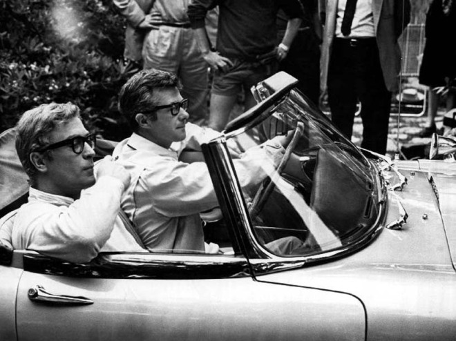 20_During filming of Deadfall in Majorca, Spain, director Bryan Forbes tests out a custom sports car for a scene as Michael Caine sits alongside, 1968.jpg